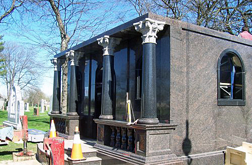 Polished tapered black granite columns of mausoleum.